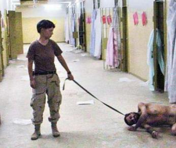 Spc. Lynndie England seen here mercilessly dragging a prisoner across the floor.