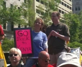 "A racist Tea-bagger holds a sign telling Obama to ""go back to Kenya!"""