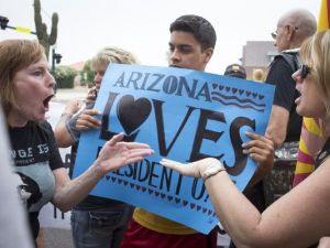 Liberal and conservative protesters who rallied in front a high school in Phoenix, AZ where President Obama was to make an appearance don't exactly see eye-to-eye.