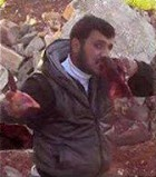 Free Syrian Army Farouq Brigade commander Abu Sakkar takes a from the heart which he ripped from the body of a pro-Assad solider