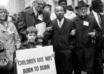 "Dr. King attends a Harlem rally protesting the Vietnam War. The child's sign read ""Children are not born to burn"", in reference to the napalm being used against Vietnamese children"