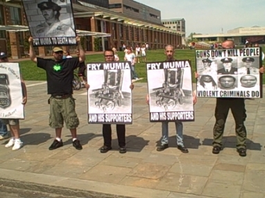 "Skinheads and racist neo-Nazis call for the reinstatement of Mumia Abu Jamal's execution date. Signs read ""Fry Mumia and his Supporters!"""