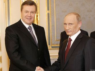 The now-ousted Ukrainian President Viktor Yanukovych shakes hands with Russian President Vladimir Putin.