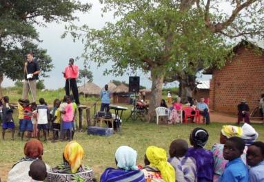 American evangelical Christian Jesse Diggs and another preacher delivering a sermon to Uganda's young. 50% of Uganda's population is below 15-16 yrs. old.