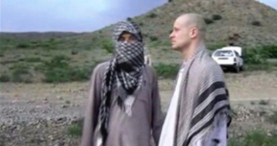 A member of the Taliban stands next to Sgt. Bowe Bergdahl awaiting U.S. forces to bring him home.