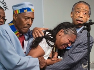 Esaw Garner (center) mourns the death of her spouse Eric Garner at the hands of the NYPD. National Action Network leader Al Sharpton is pictured at right.