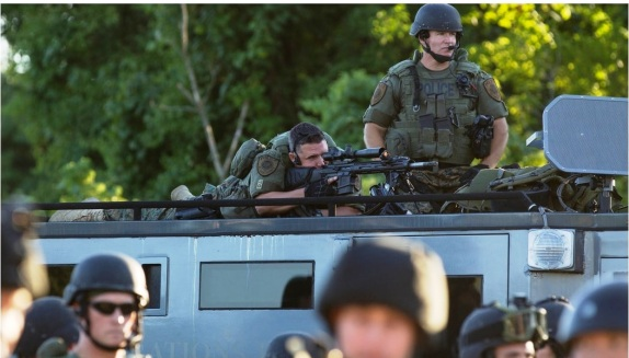 Ferguson Police in their riot gear aiming assault weapons into crowds of unarmed demonstrators.