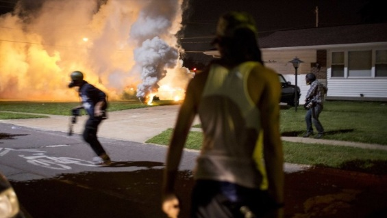 News crew retreats from the sidewalk in front of a front yard after St. Louis police in Ferguson fire tear gas and explosives into a resident's front yard.