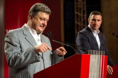 Petro Poroshenko speaks to the press in Ukraine, with Mayor-elect Vitali Klitschko to his left.