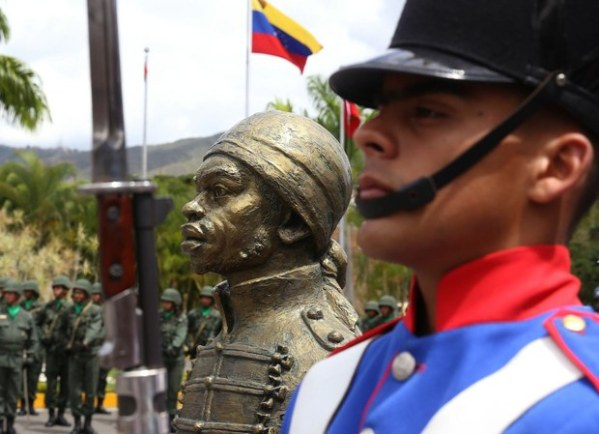 Venezuelan army officer next to statue of Pedro Camejo, the Black soldier who deserted the Spanish colonial army in order to fight for Venezuela's Independence.
