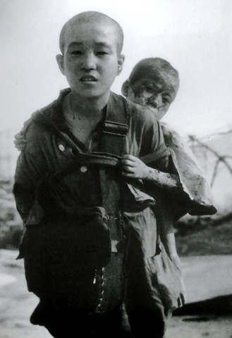 Nagasaki. August 10, 1945. An orphaned Japanese youth carries his brother after an atomic bomb was dropped on their residence.