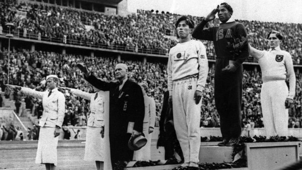 Jesse Owens (center) wins one of four Gold Medals for track and field at the 1936 Olympic Games in Berlin, Germany, at the time under Nazi rule.